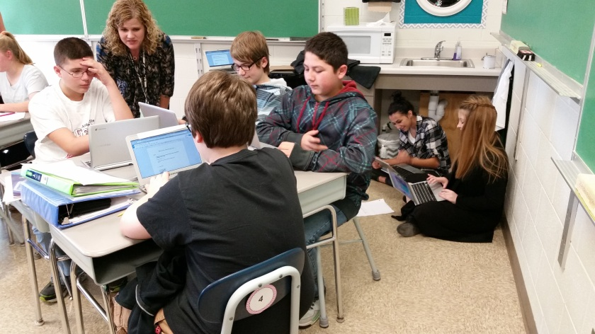 In their desks and on the floor, students collaborate under Julie's guidance.